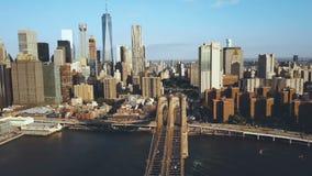 Flyg- sikt av den Brooklyn bron i New York, USA som går till det Manhattan området Amerikanska flaggan som vinkar på vinden stock video