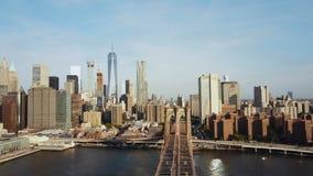 Flyg- sikt av den Brooklyn bron med amerikanska flaggan som vinkar på vinden Scenisk sikt av East River, Manhattan i New York stock video
