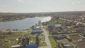 Flyg- sikt av den europeiska byn nära dammet Härlig flyg- sikt av färg sjön och byn med kyrkan Top beskådar Royaltyfri Foto