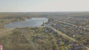 Flyg- sikt av den europeiska byn nära dammet Härlig flyg- sikt av färg sjön och byn med kyrkan Top beskådar Arkivbilder