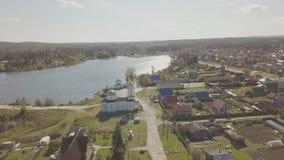 Flyg- sikt av den europeiska byn nära dammet Härlig flyg- sikt av färg sjön och byn med kyrkan Top beskådar Royaltyfri Fotografi