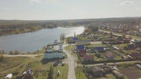 Flyg- sikt av den europeiska byn nära dammet Härlig flyg- sikt av färg sjön och byn med kyrkan Top beskådar Fotografering för Bildbyråer