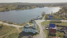 Flyg- sikt av den europeiska byn nära dammet Härlig flyg- sikt av färg sjön och byn med kyrkan Top beskådar Royaltyfria Bilder