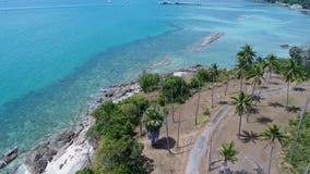 Flyg- sikt av den havskustlinjen och ön med palmträd med pir i bakgrunden arkivbilder