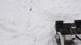 Flyg- sikt av den kompakta traktoren med snö som plogar den rengörande parkeringsplatsen för utrustning arkivfilmer