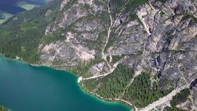Flyg- sikt av den kristallklara sjön Lago di Braies och steniga berg arkivfilmer