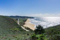 Flyg- sikt av den kust- huvudvägen som passerar längs en sandig strand i Montara, Kalifornien royaltyfri foto