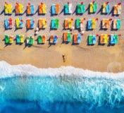 Flyg- sikt av den liggande kvinnan på stranden med färgrika chaise-vardagsrum fotografering för bildbyråer