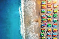 Flyg- sikt av den liggande kvinnan på stranden med färgrika chaise-vardagsrum royaltyfri fotografi