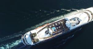 Flyg- sikt av den lyxiga medelseglingen för kryssningskepp från port på soluppgång stock video