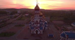 Flyg- sikt av den nya kyrkan på gryning i liten stad härlig himmel i soluppgång 4K arkivfilmer