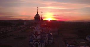 Flyg- sikt av den nya kyrkan på gryning i liten stad härlig himmel i soluppgång 4K stock video