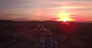 Flyg- sikt av den nya kyrkan på gryning i liten stad härlig himmel i soluppgång 4K lager videofilmer