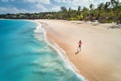 Flyg- sikt av den rinnande unga kvinnan på den sandiga stranden arkivbild
