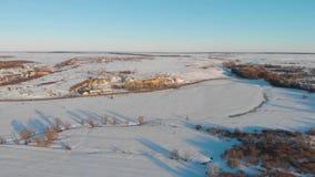 Flyg- sikt av den sm? byn och v?gar i vintern, vinterlandskap arkivfilmer