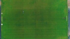 Flyg- sikt av den stora gräsklipparen som klipper grönt gräs i ett fotbollfält 4K arkivfilmer