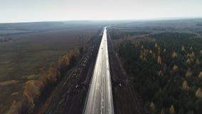 Flyg- sikt av den tjocka skogen i höst med vägklipp igenom lager videofilmer