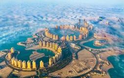 Flyg- sikt av denQatar ön i Doha till och med morgondimman - Qatar, Persiska viken arkivfoto