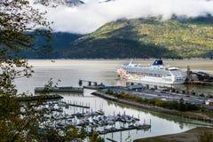 Flyg- sikt av det norska för solkryssning för kryssningslinje som NCL skeppet anslutas i staden av Skagway i Alaska royaltyfri fotografi