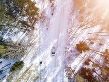 Flyg- sikt av en bil på vintervägen Vinterlandskapbygd Flygfotografering av den snöig skogen med en bil på vägen capt. royaltyfria foton