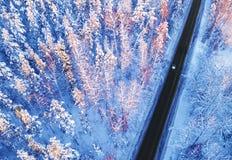 Flyg- sikt av en bil p? vinterv?gen i bygden f?r skogvinterlandskap Flygfotografering av den sn?ig skogen med en bil p? arkivbilder