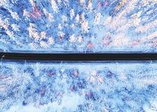 Flyg- sikt av en bil p? vinterv?gen i bygden f?r skogvinterlandskap Flygfotografering av den sn?ig skogen med en bil p? fotografering för bildbyråer