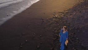 Flyg- sikt av en flicka i en blå klänning som går på stranden med svart sand kanarief?gel?ar spain tenerife stock video