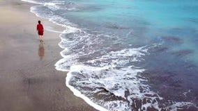 Flyg- sikt av en flicka i en röd klänning som går på stranden med svart sand kanariefågelöar spain tenerife stock video
