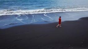 Flyg- sikt av en flicka i en röd klänning som går på stranden med svart sand kanariefågelöar spain tenerife lager videofilmer