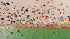 Flyg- sikt av en fullsatt strand i en solig varm dag Gul sand och paraplyer