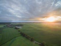 Flyg- sikt av en härlig solnedgång över fält för grön havre - jordbruks- fält Royaltyfri Fotografi