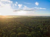 Flyg- sikt av en härlig solnedgång över lantligt landskap med skogar och gräsplanfält Arkivbilder