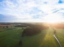 Flyg- sikt av en härlig solnedgång över lantligt landskap med skogar och gräsplanfält Royaltyfri Fotografi