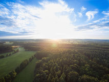 Flyg- sikt av en härlig solnedgång över lantligt landskap med skogar och gräsplanfält Royaltyfria Foton