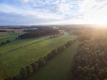 Flyg- sikt av en härlig solnedgång över lantligt landskap med skogar och gräsplanfält Royaltyfri Bild
