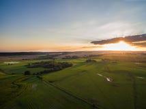 flyg- sikt av en härlig solnedgång med ovannämnda gröna jordbruks- fält för solstrålar i sommar Royaltyfri Bild