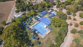 Flyg- sikt av en klubbhus med den blåa simbassängen royaltyfri foto