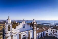 Flyg- sikt av en kyrklig fasad i den historiska byn av Monsaraz i Alentejo med den Alqueva fördämningbehållaren på bakgrunden Royaltyfria Foton