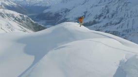 Flyg- sikt av en personskidåkning i ultrarapid i berg som täckas med snö lager videofilmer