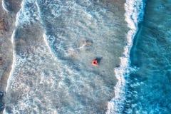 Flyg- sikt av en simma kvinna i det blåa havet med vågor arkivbilder
