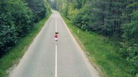 Flyg- sikt av en skogväg och en slank spring för ung kvinna till och med den lager videofilmer