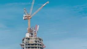 Flyg- sikt av en skyskrapa under konstruktion med enorma kranar i Dubai timelapse f?renade arabiska emirates arkivfilmer