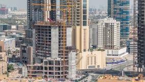Flyg- sikt av en skyskrapa under konstruktion med enorma kranar i Dubai timelapse f?renade arabiska emirates stock video