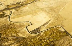 Flyg- sikt av en slingrig flod som omges av det gula vetefältet Royaltyfria Foton