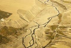 Flyg- sikt av en slingrig flod som omges av det gula vetefältet Arkivfoton