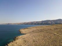 Flyg- sikt av en slingrig väg som kör längs de kroatiska kusterna, grusvägen, ön av Pag nära den Rucica stranden i Metajna croati Royaltyfria Foton