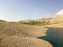 Flyg- sikt av en slingrig väg som kör längs de kroatiska kusterna, grusvägen, ön av Pag nära den Rucica stranden i Metajna croati Arkivfoton