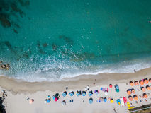 Flyg- sikt av en strand med kanoter, fartyg och paraplyer royaltyfria bilder