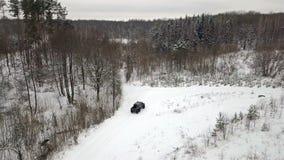 Flyg- sikt av en 6x6 SUV, som rider på entäckt väg i vinterskog lager videofilmer