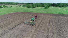 Flyg- sikt av en traktor med en planterflyttning till och med fältet arkivfilmer